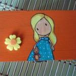 Cajita de madera decorada con muñequita y detalles de fieltro naranja