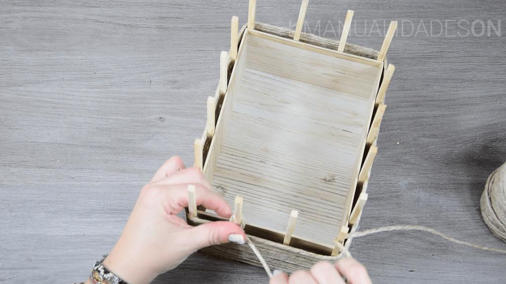 Cogemos la cuerda y la vamos enrollando desde la base alrededor de la caja. Para que quede bien unida la cuerda hacia la caja vamos echando pegotes de silicona en los palos para que se vaya quedando bien colocada.